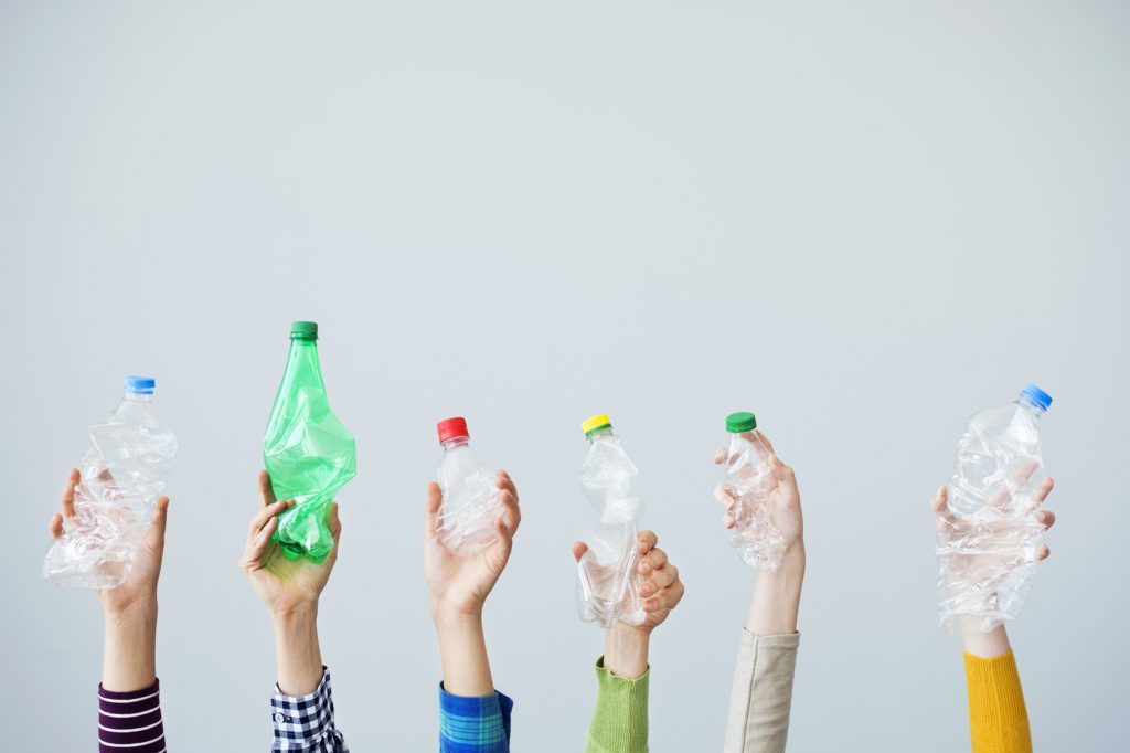 hands holding up plastic bottles